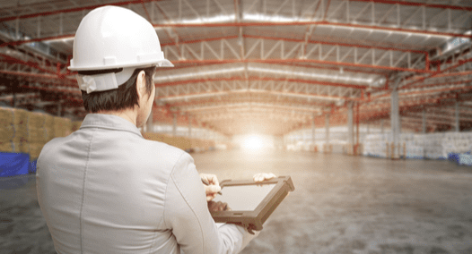 Energy auditor standing in warehouse with clipboard